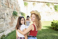 Spain, Mallorca, Palma, two female friends smiling at camera while another friend is taking a picture of them - IGGF00486