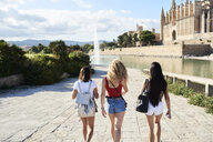Spain, Mallorca, Palma, rear view of three young women exploring in the city - IGGF00489