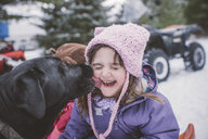 Young girl with dog in snowy landscape, dog licking girl's face - ISF01393
