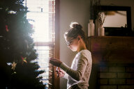Girl putting up Christmas decorations - ISF01402