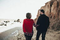 Rear view of romantic mid adult couple strolling on beach, Odessa Oblast, Ukraine - ISF01423