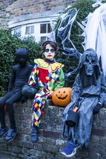 Portrait of three boys in halloween costumes, sitting on wall - ISF01447
