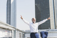 Happy mature businessman cheering in the city - UUF13666