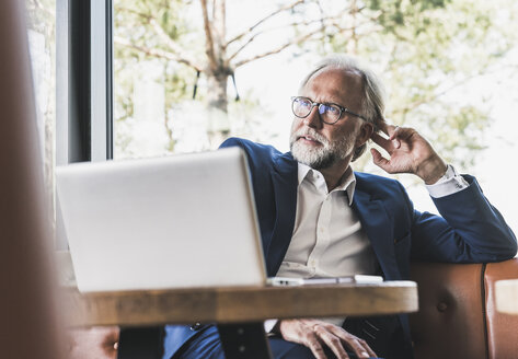 Mature businessman sitting at table in a cafe with laptop - UUF13675