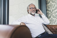 Smiling mature businessman sitting in armchair talking on cell phone - UUF13681