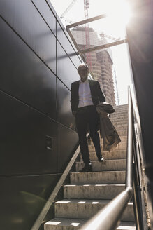 Mature businessman walking on staircase in the city - UUF13684