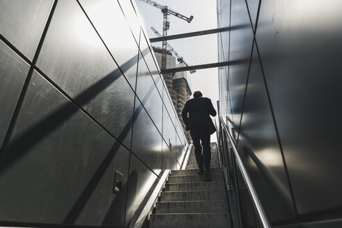 Businessman walking on staircase in the city - UUF13687