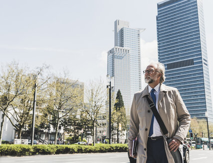 Confident mature businessman in the city looking around - UUF13690