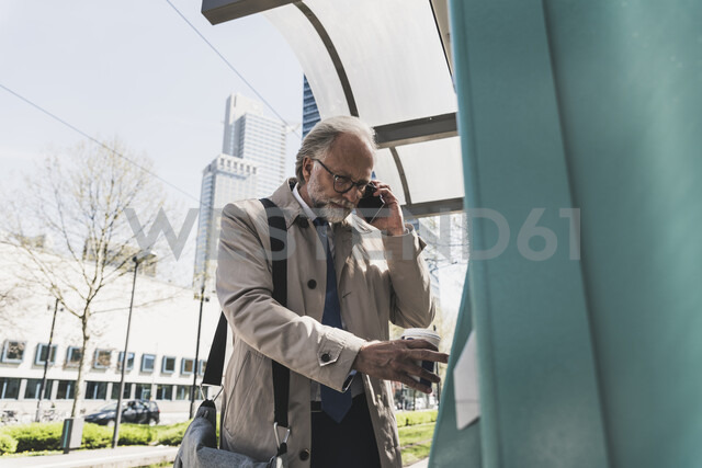 Mature businessman with cell phone and takeaway coffee in the city at tram station - UUF13696 - Uwe Umstätter/Westend61
