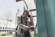 Mature businessman with cell phone and takeaway coffee in the city at tram station - UUF13696