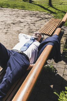 Mature businessman lying on a bench listening to music - UUF13699