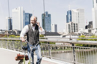 Smiling mature man with earbuds and bicycle crossing bridge in the city - UUF13702
