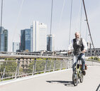 Smiling mature man on bicycle crossing bridge in the city - UUF13705