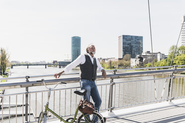 Mature man with bicycle listening to music on bridge in the city - UUF13708