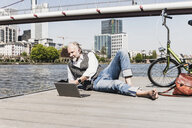 Mature man with laptop, earbuds and bicycle lying at the riverside in the city - UUF13711