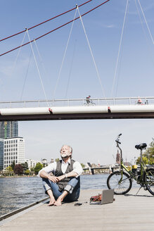 Mature man with laptop and bicycle sitting at the riverside in the city - UUF13714