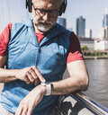 Athletic mature man with headphones taking the time on bridge in the city - UUF13720