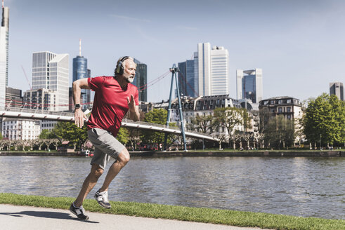 Mature man with headphones running at the riverside in the city - UUF13723