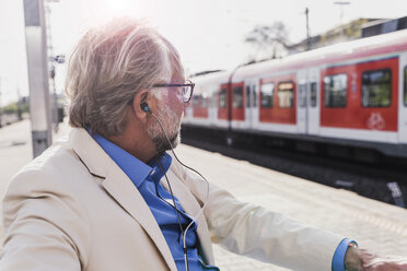 Mature businessman with earbuds sitting at train station - UUF13729