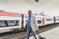 Mature businessman walking at train platform with earbuds and suitcase - UUF13732