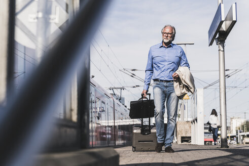 Mature businessman walking at train platform with suitcase and briefcase - UUF13735