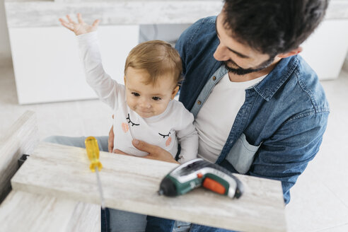 Father and daughter assembling a wooden table at home - JRFF01649