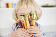 Portrait of cute girl in kitchen holding bunch of colourful carrots to her face - CUF05722