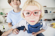 Portrait of cute girl in eye glasses with brother in kitchen - CUF05728