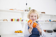 Cut girl looking at oranges in kitchen - CUF05761