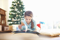 Girl lying on living room floor reading book at christmas - CUF05770