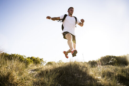 Young man training, jumping mid air from sand dunes - CUF05881