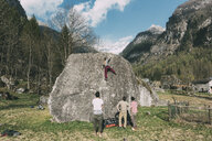 Rear view of adult bouldering friends watching young woman climb boulder, Lombardy, Italy - CUF05905