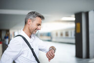 Mature businessman looking at wristwatch on train station platform - CUF05929