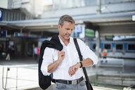 Mature businessman looking at wristwatch in train station - CUF05932