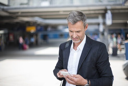Mature businessman looking at smartphone in train station - CUF05935