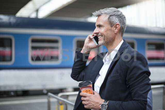 Mature businessman making smartphone call on train station platform - CUF05938