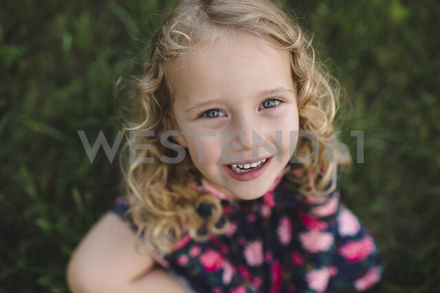 Overhead portrait of blond haired girl on grass - CUF05965