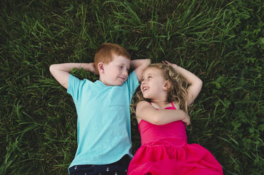 Overhead portrait of boy and sister lying on grass looking at each other - CUF05968