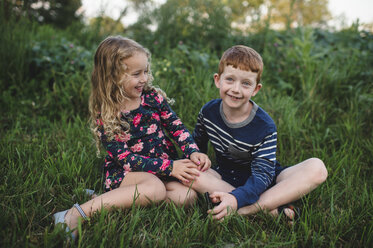 Girl and brother sitting in field - CUF05971
