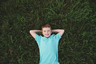 Overhead portrait of red haired boy lying on grass - CUF05977