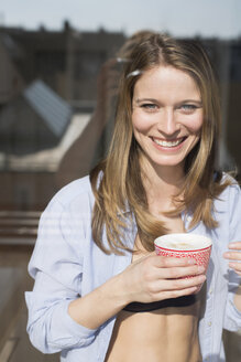 Portrait of beautiful woman wearing open shirt holding coffee  at window - CUF06370