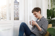 Happy woman sitting relaxed at window, drinking coffee - FKF02887