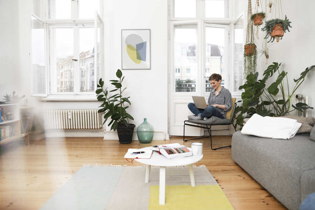 Woman sitting in chair at home, using laptop - FKF02890 - Florian Küttler/Westend61