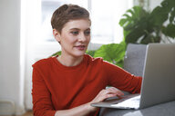 Woman sitting at home, using laptop - FKF02914