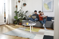 Family sitting on couch, using laptop - FKF02917
