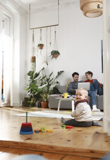Parents sitting on couch, using laptop, while daughter is playing on the floor - FKF02920