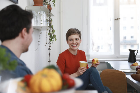 couple sitting in kitchen, talking, woman eating apple - FKF02932