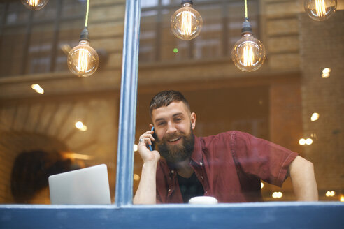 Window view of young man making smartphone call in cafe - CUF06476