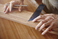 Hands of male carpenter using set square at workbench - CUF06521