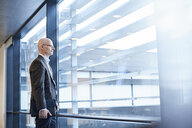 Mature businessman looking through office window - CUF06530